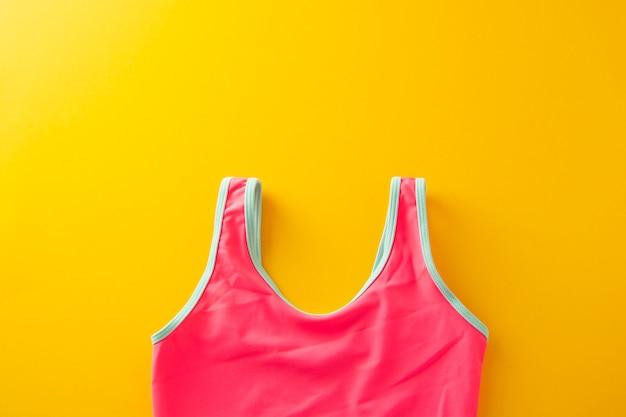 Gelber hintergrund der sommerferien mit rosa badeanzug. kopieren sie platz.