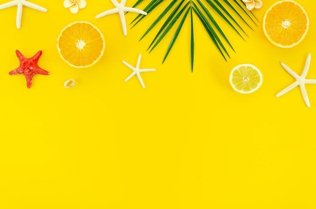 Gelber hintergrund des sommers mit palmblattzweig, -starfishes und -orangen
