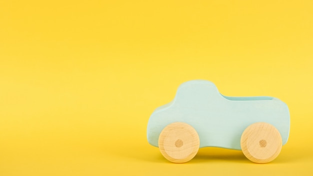 Gelber hintergrund mit blauem spielzeugauto und copyspace der kinder