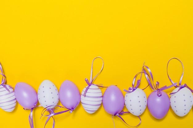 Gelber hintergrund mit dekorativen ostereier in reihe