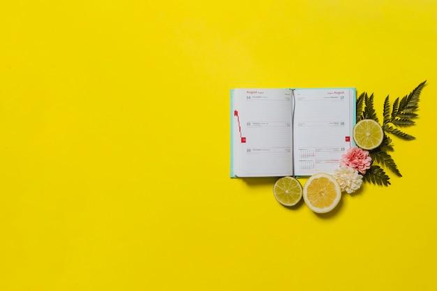 Gelber hintergrund mit kalender und zitrusfrüchten