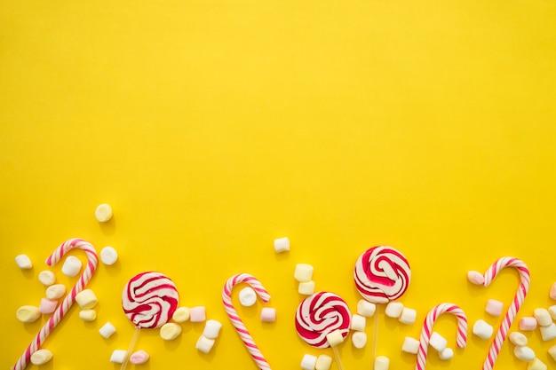 Gelber hintergrund mit zuckerstangen, lutscher und marshmallows