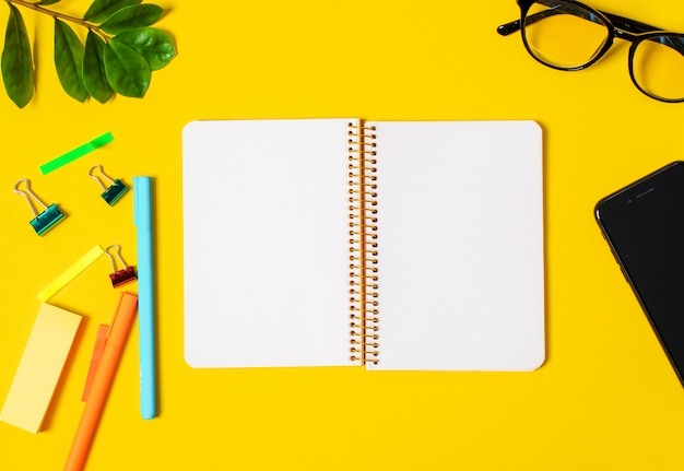 Gelber hintergrund, weißes notizbuch für aufzeichnungen, telefon, computerbrille, zweigpflanzen, stifte, bleistifte.