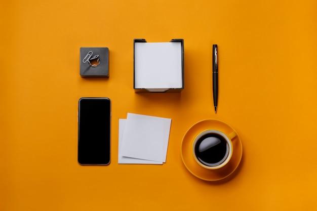 Gelber hintergrunddesktopgeschäftstelefonbriefpapierkaffeetasse-büroklammerstift