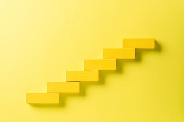 Gelber holzblock, der als stufentreppe für erfolg stapelt