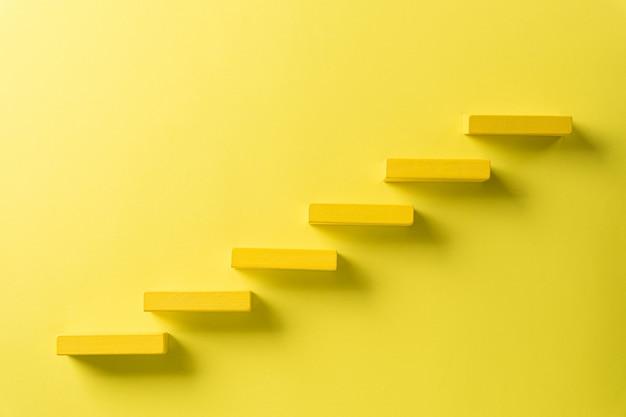 Gelber holzblock, der als stufentreppe stapelt
