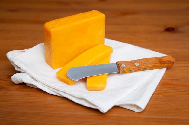 Gelber käse und messer, die auf weißes tuch legen