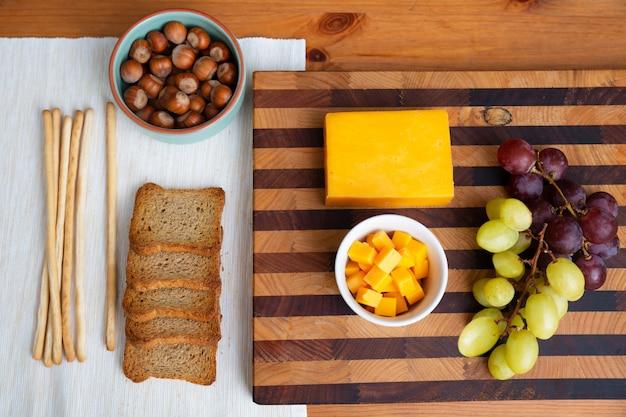 Gelber käse und trauben, die auf holzbrett legen