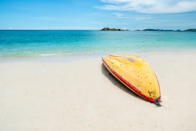 Gelber kajak am tropischen strand am schönen vollen tag.