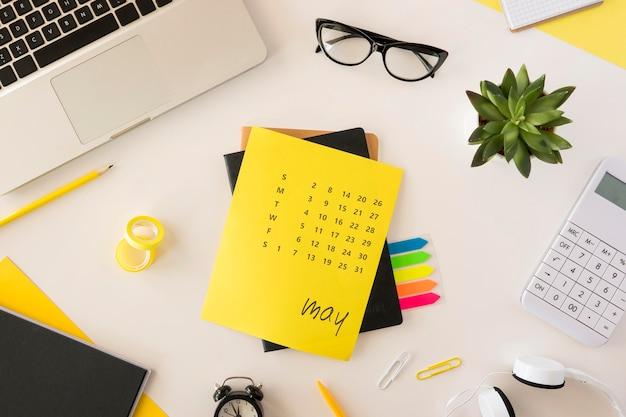 Gelber kalender des schreibtischs der draufsicht