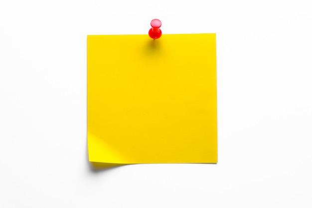 Gelber klebriger aufkleber auf einem weißen hintergrund zur erinnerung an informationen, angebracht mit einer büroklammer. platz für text.