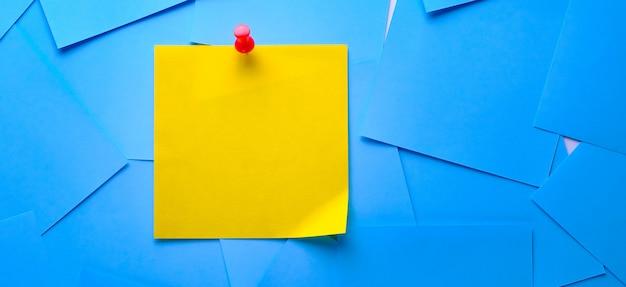 Gelber klebriger aufkleber zur informationsanzeige. platz für text. nahe bei ihm sind leere blaue aufkleber. banner
