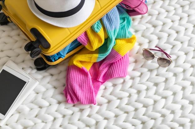 Gelber koffer von oben mit den notwendigen dingen, die sich auf den sommerurlaub auf strickplaid vorbereiten