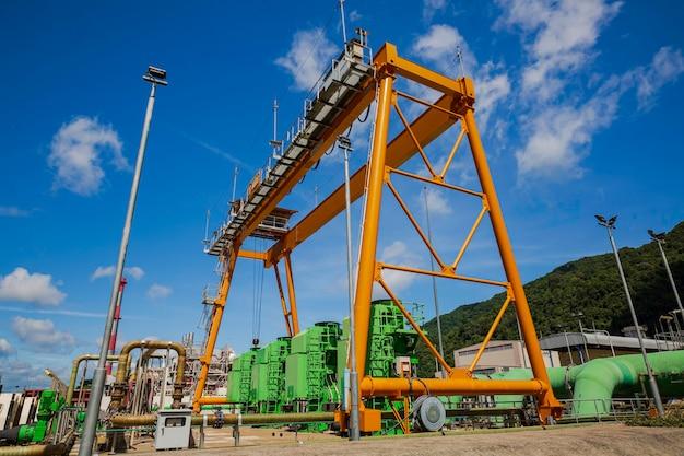 Gelber kran im frachthafen, der kohle übersetzt. industrielle szene. ladekran bei sonnenuntergang