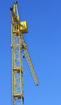 Gelber kran und blauer himmel auf der baustelle