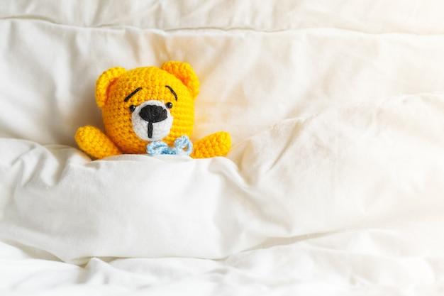 Gelber kranker teddybär, der im bett auf weiß liegt.