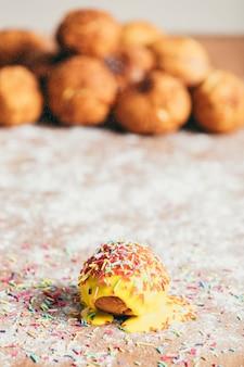 Gelber krapfen mit zuckersträngen verziert
