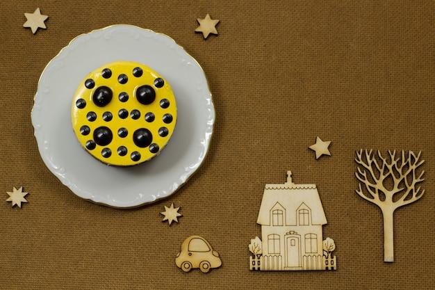 Gelber kuchen auf einer weißen platte. auf einem dunklen hintergrund symbole: holz, haus, auto