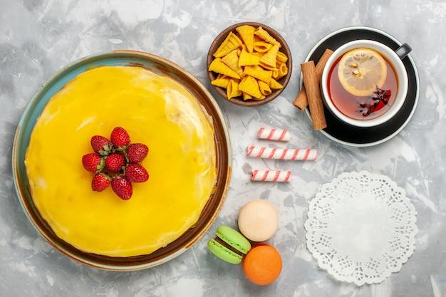 Gelber kuchen der draufsicht mit erdbeerkuchen und tasse tee auf weißem hintergrund
