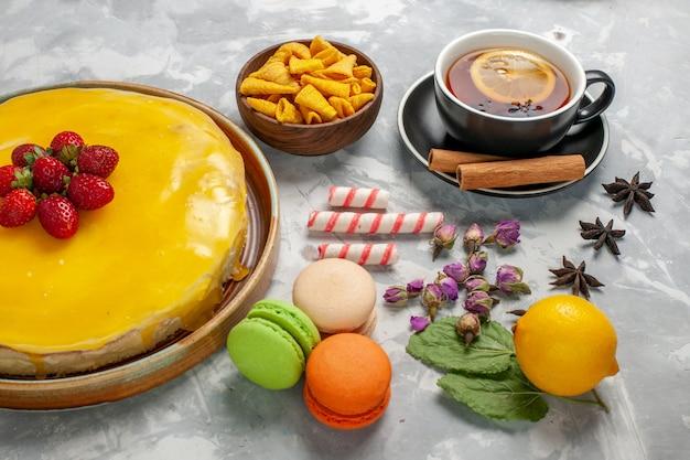Gelber kuchen der vorderansicht mit macarons und tasse tee auf hellweißer oberfläche