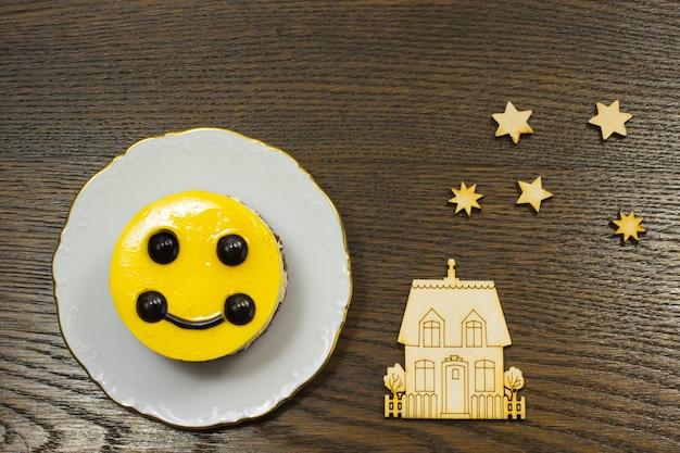 Gelber kuchen, hausikonen und sterne auf einem dunklen hintergrund