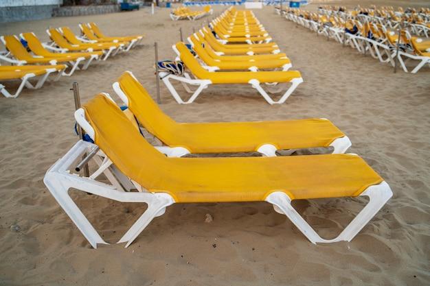Gelber liegestuhl am strand