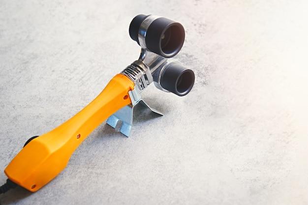 Gelber lötkolben für pvc-pp-rohre auf sanitärwerkzeug mit grauem hintergrund mit kopierraum-soft-fokus