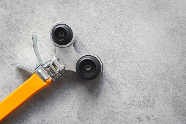 Gelber lötkolben für pvc-rohre auf grauem hintergrund mit kopierraum.