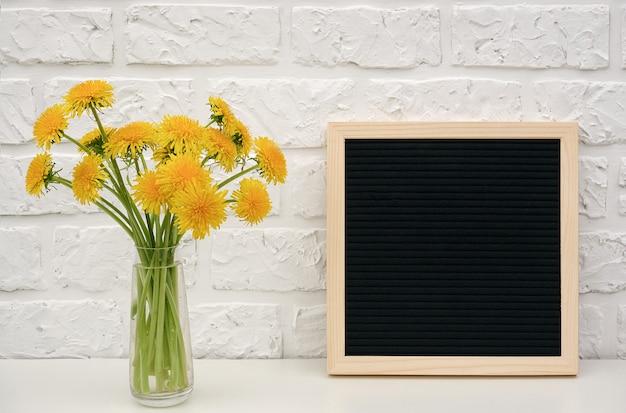 Gelber löwenzahn des blumenstraußes im vase und in der leeren tafel der schwarzen schrift auf tabelle