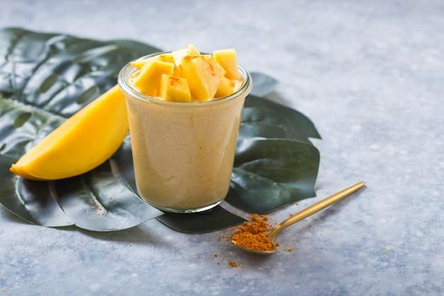 Gelber mangojoghurt oder smoothie auf grauem hintergrund. kurkuma lassie oder lassi in glas.