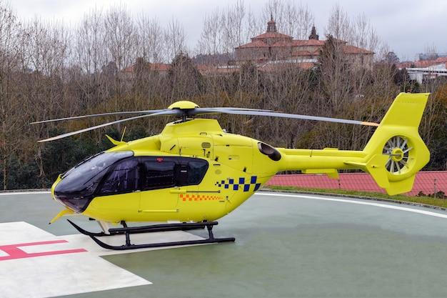 Gelber medizinischer hubschrauber auf der landebahn eines krankenhauses