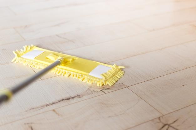 Gelber mopp zu hause. mikrofasermopp isoliert auf weißem holzbodenhintergrund, nahaufnahme