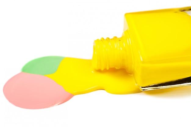 Gelber nagellack verschüttet lokalisiert auf weißem hintergrund
