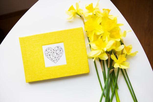 Gelber narzissenstrauß und gelbes buch auf weißem tisch