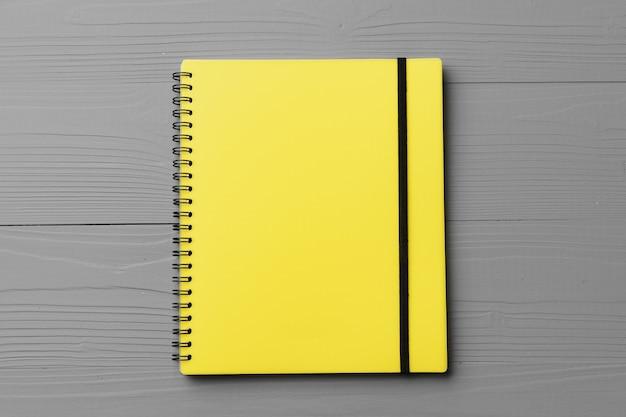 Gelber notizblock auf grauem hölzernem hintergrund