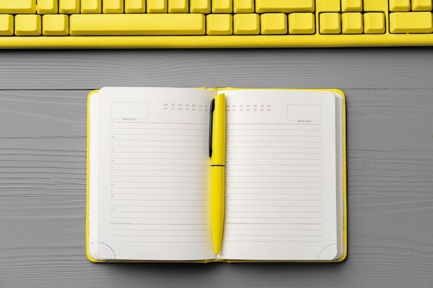 Gelber notizblock auf grauem holz