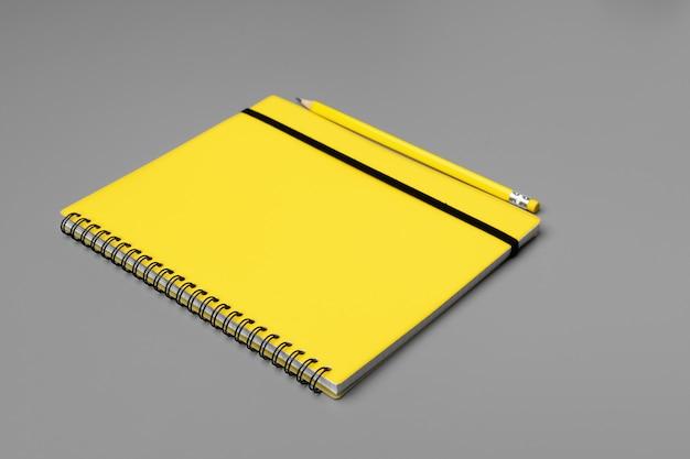 Gelber notizblock mit gelbem stift auf grau