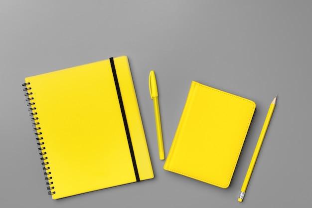 Gelber notizblock mit gelbem stift auf grauem hintergrund schließen oben