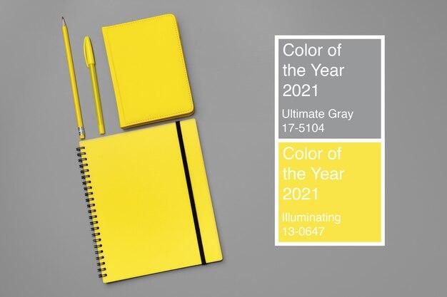Gelber notizblock mit gelbem stift auf grauer nahaufnahme