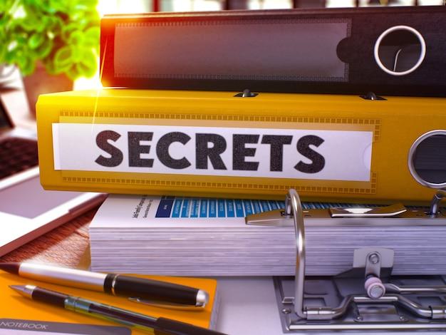 Gelber office-ordner mit inschrift-geheimnissen auf dem office-desktop mit bürobedarf und modernem laptop. geheimnisse geschäftskonzept auf unscharfen hintergrund. geheimnisse - getöntes bild. 3d.
