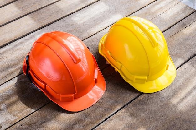Gelber, orange harter schutzhelmbauhut für sicherheitsprojekt des arbeiters als ingenieur oder arbeitskraft