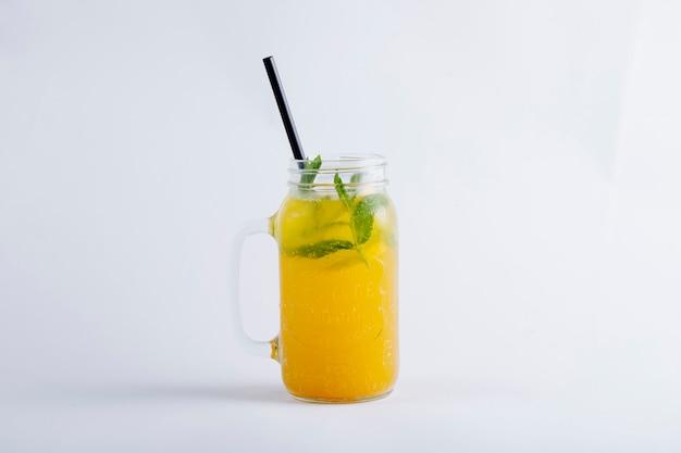 Gelber orangensaft in einem glasgefäß mit tadellosen blättern.