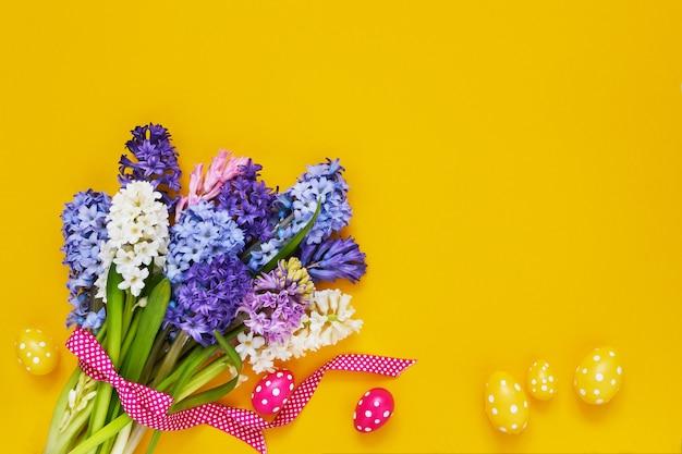 Gelber osterhintergrund. frühlingsblumen und dekorative ostereier auf gelbem hintergrund. speicherplatz kopieren
