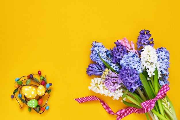 Gelber ostertisch. frühlingsblumen und dekorative ostereier. speicherplatz kopieren, draufsicht.