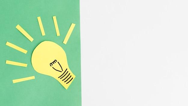 Gelber papierausschnitt der glühlampe über dem grünen hintergrund mit kopienraum