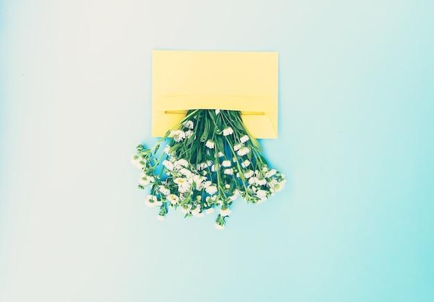 Gelber papierumschlag mit kleinen gartenweißen kamillenblüten auf hellblauem hintergrund. festliche blumenvorlage. grußkarten-design. ansicht von oben. vintage-stil.