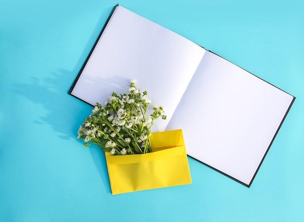 Gelber papierumschlag mit kleinen gartenweißen kamillenblüten und leerem geöffnetem notizblock auf hellblauem hintergrund. festliche blumenvorlage. grußkarten-design. ansicht von oben.