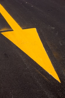 Gelber pfeil auf asphalt