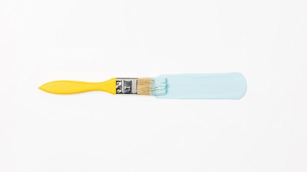 Gelber pinsel der draufsicht mit blauer farbe
