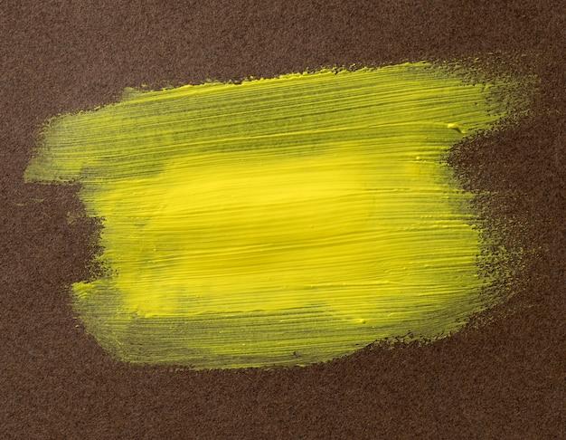 Gelber pinselstrich auf strukturiertem hintergrund